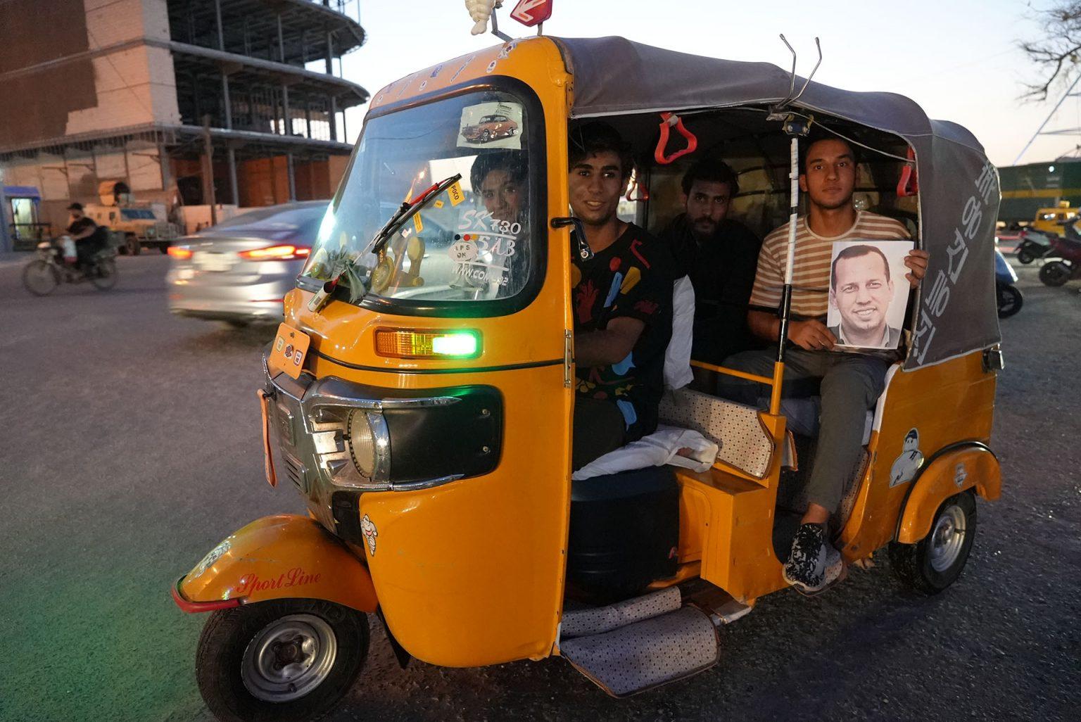 Young people in tuk-tuk in Basra display portrait of slain journalist